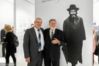 Meir Shapira and Rabbi dr Moshe Pinchuk standing in front of a portrait of Meir Shapira.